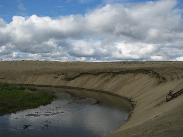 Ahnewetut Creek in the Kobuk River Valley, with river, sand dunes, and clouds. Photo: NPS